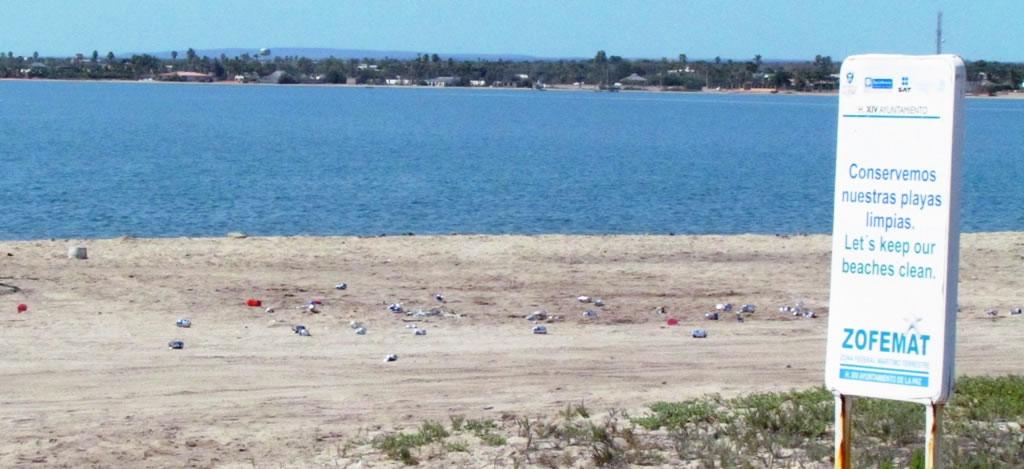Beach litter beside No Littering sign near La Paz, Mexico