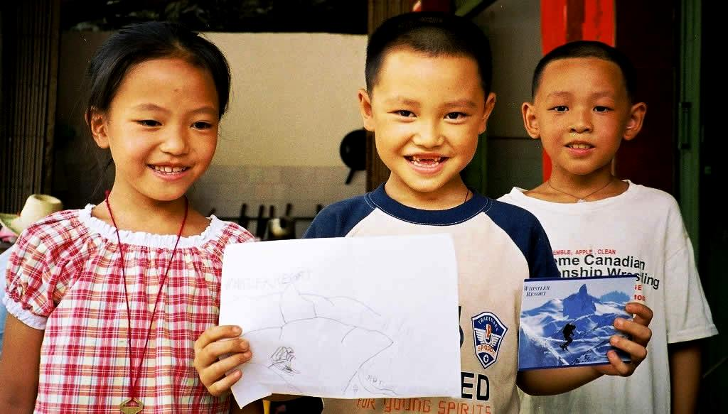 Trading postcards and T-shirts with local children in Longshen, China